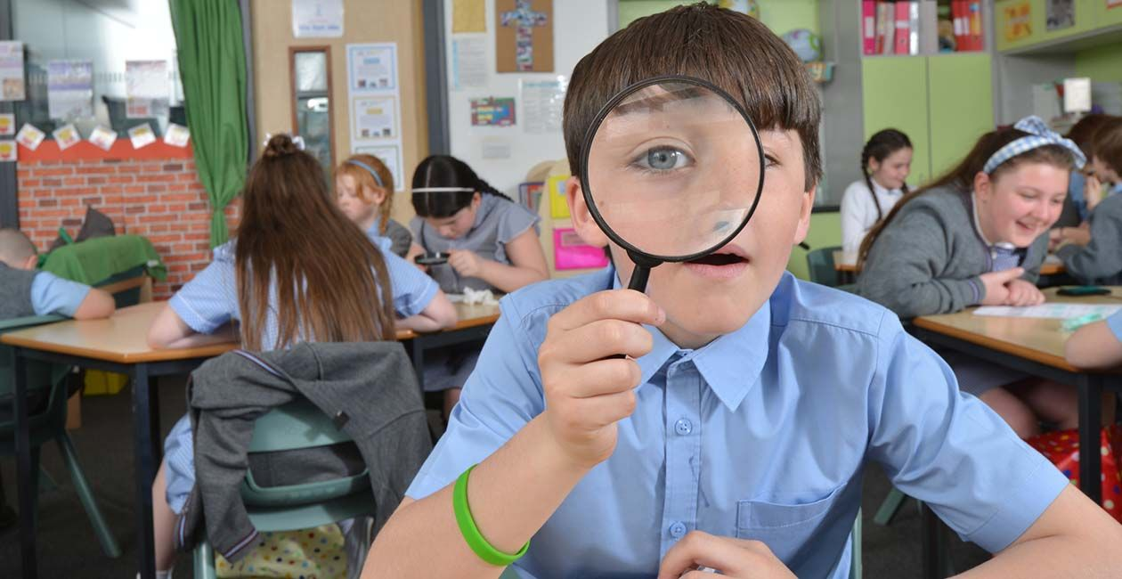 Boy in classroom looking through a magnifying glass